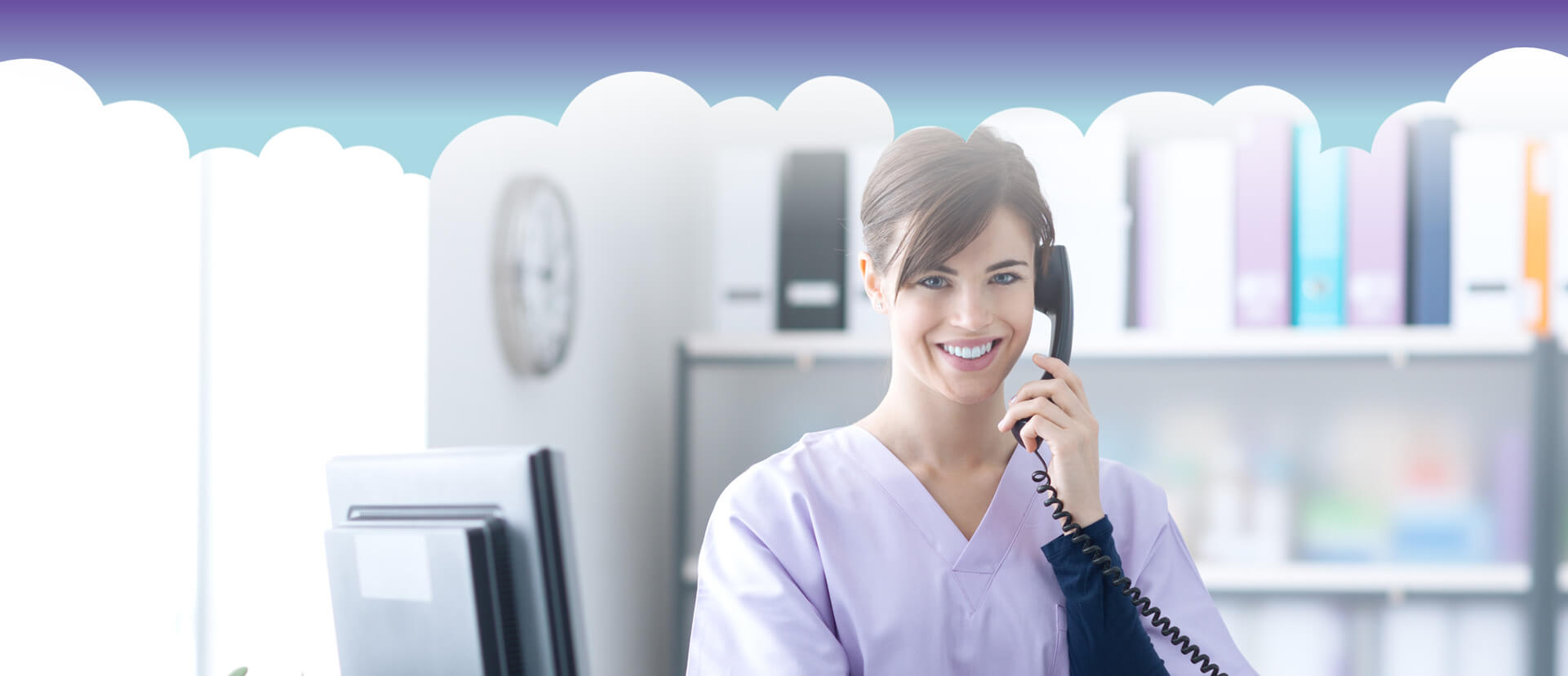 Dental receptionist answering a phone call smiling at the camera