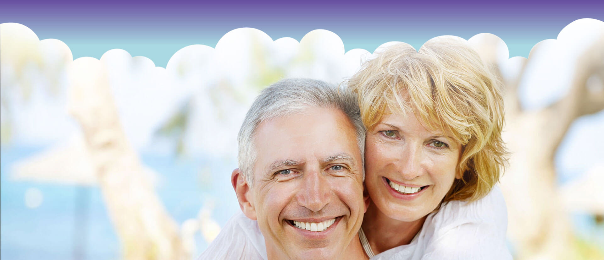 Elderly couple with dentures embracing each other smiling at the camera